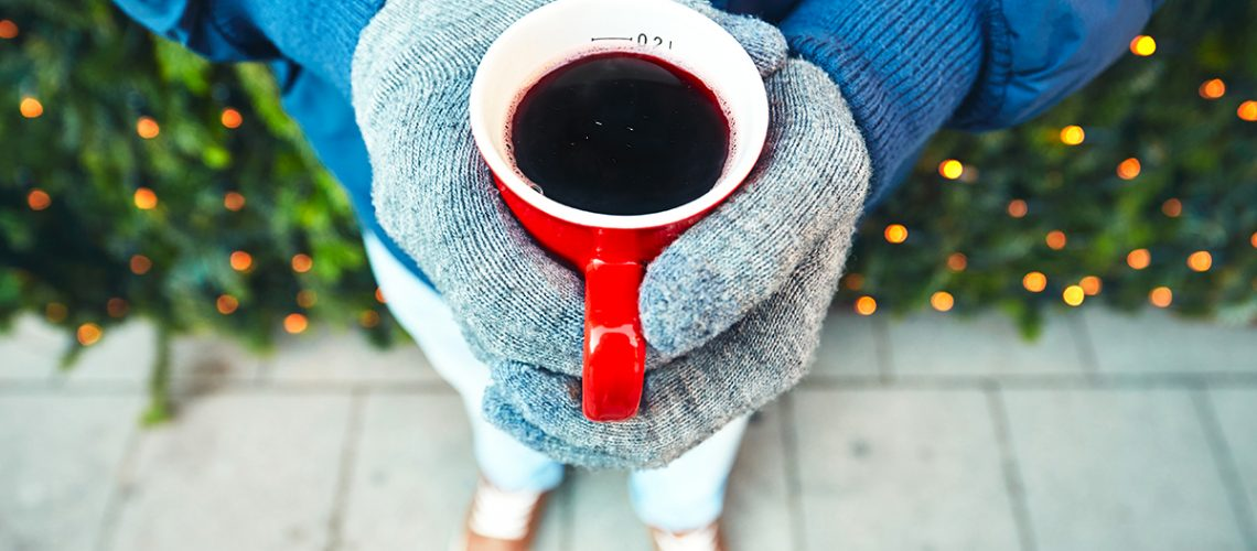Man holding cup of the hot wine at the Christmas market - Munich, Germany